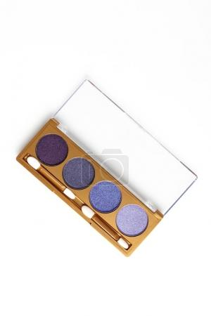 top view of opened case with different shaded purple cosmetic eye shadows isolated on white