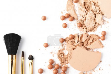 top view of nude color cosmetic powder with brushes isolated on white