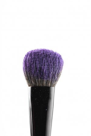purple cosmetic powder on makeup brush isolated on white