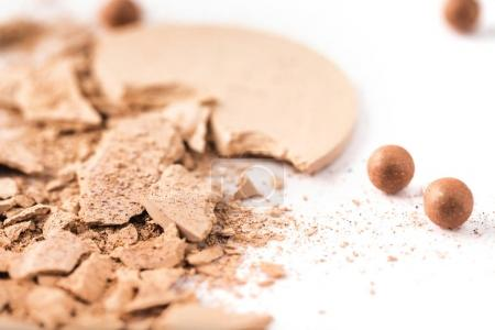 close-up shot of cracked cosmetic powder isolated on white