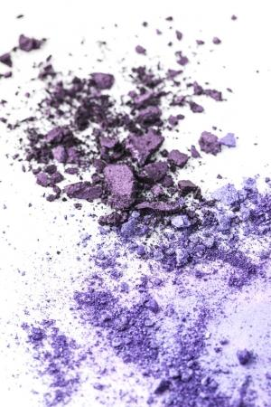crushed purple cosmetic eye shadows on white tabletop