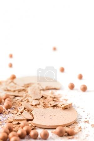 crushed cosmetic powder lying on white surface