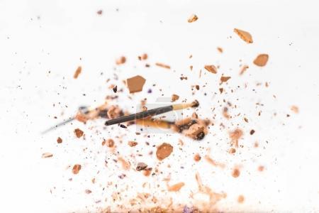 Photo pour Poudre cosmétique broyée avec pinceaux de maquillage tombant isolé sur blanc - image libre de droit