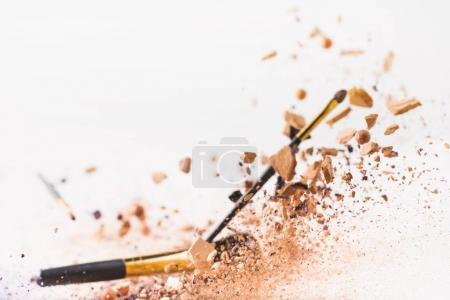 pieces of cosmetic powder with makeup brushes falling isolated on white