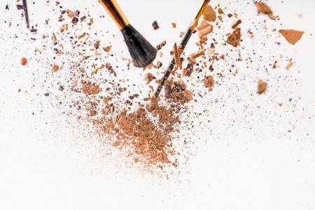 pieces of cosmetic powder with brushes falling isolated on white