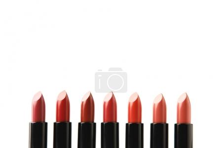 row of lipsticks of various shades isolated on white