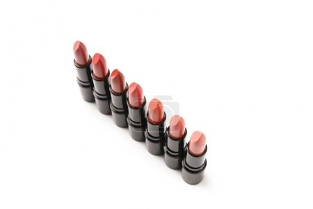 high angle view of row of lipsticks of various shades isolated on white