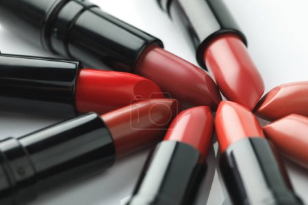 close-up shot of red lipsticks of various shades on white tabletop