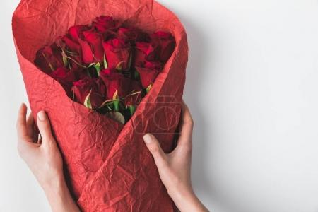 partial view of woman holding bouquet of red roses in wrapping paper for st valentines day isolated on white