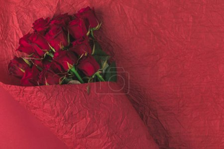 top view of bouquet of roses in wrapping paper isolated on red