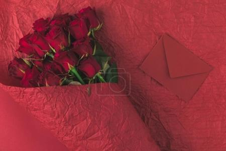 top view of bouquet of roses in wrapping paper and envelope isolated on red, st valentines day concept