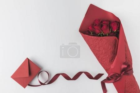 Photo for Flat lay with bouquet of roses, ribbon and envelope isolated on white, st valentines day holiday concept - Royalty Free Image
