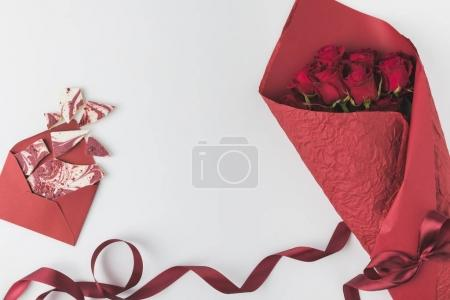 flat lay with arrangement of bouquet of red roses with ribbon and envelope with sweet dessert isolated on white, st valentines day concept