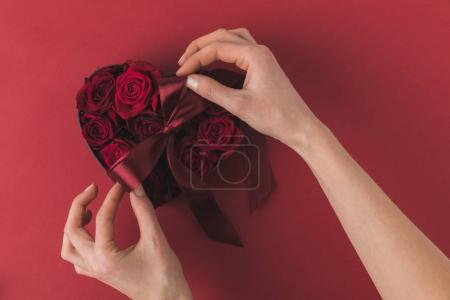 partial view of woman tying ribbon on heart shaped box with roses on red tabletop, st valentines day concept