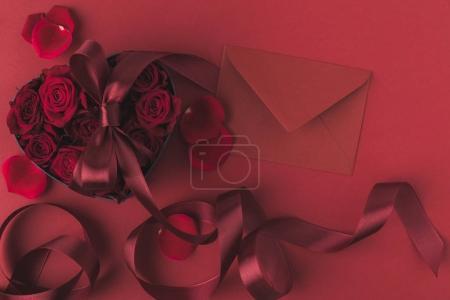 Photo pour Vue de dessus des roses en coeur en forme de boîte de cadeau avec ruban et enveloppe isolée sur le rouge, le concept de vacances st valentin - image libre de droit