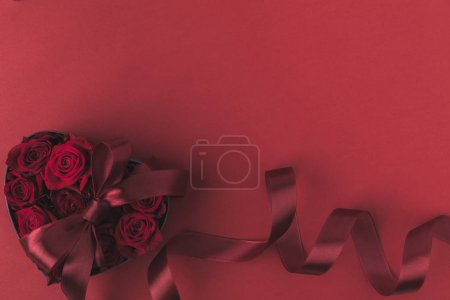 top view of roses in heart shaped gift box with ribbon isolated on red, st valentines day holiday concept