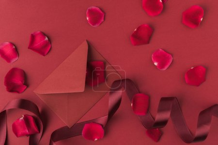 flat lay with arranged red roses petals, envelope and ribbon isolated on red, st valentines day concept