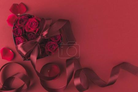 top view of roses in heart shaped gift box with ribbon and petals isolated on red, st valentines day holiday concept