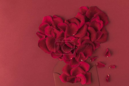 Photo for Top view of heart made of roses petals and envelope isolated on red, st valentines day concept - Royalty Free Image
