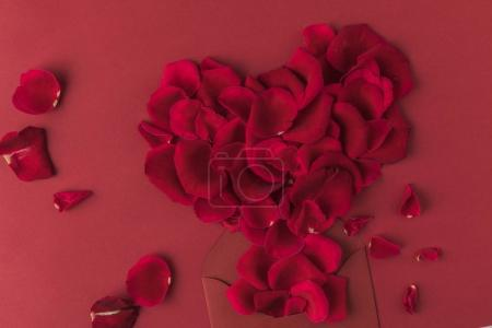 top view of heart made of roses petals and envelope isolated on red