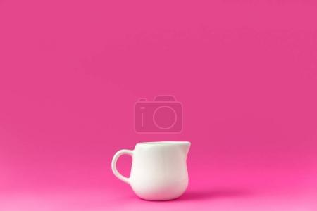 Photo for Close-up view of single empty white jug ready for breakfast isolated on pink - Royalty Free Image