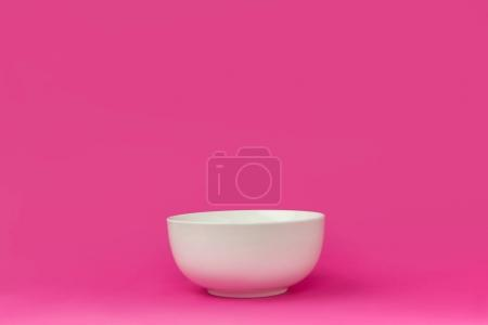 close-up view of single empty white bowl ready for breakfast isolated on pink