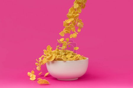 close-up view of sweet crunchy corn flakes falling into white bowl isolated on pink