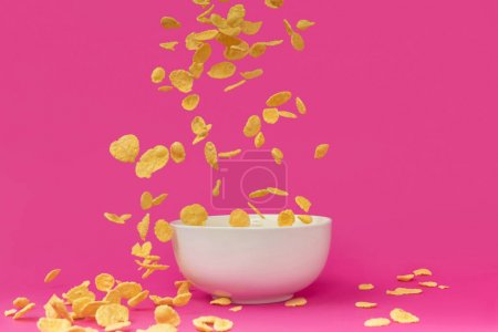 close-up view of delicious crunchy corn flakes falling into white bowl isolated on pink
