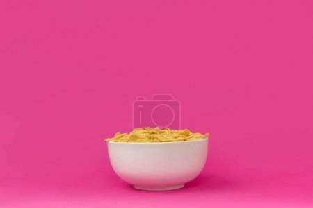 close-up view of white bowl with healthy tasty crunchy corn flakes isolated on pink
