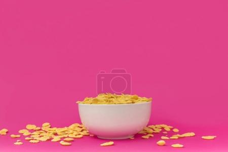 close-up view of white bowl with tasty crunchy corn flakes on pink