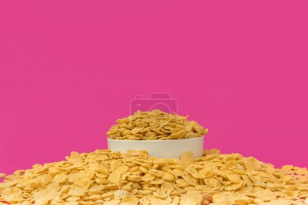 close-up view of white bowl with sweet crunchy corn flakes isolated on pink