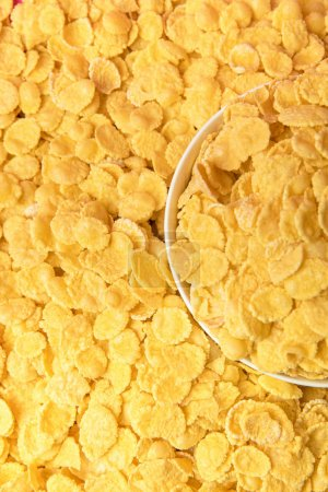 Photo for Top view of tasty crispy corn flakes and white bowl - Royalty Free Image