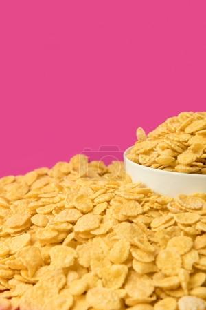 close-up view of fresh crunchy corn flakes and white bowl isolated on pink