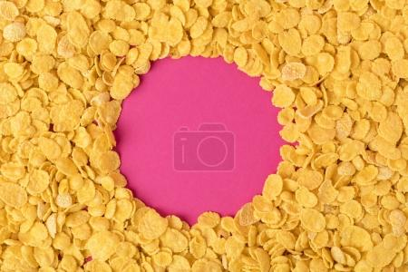 Photo for Top view of circle made in healthy organic corn flakes on pink - Royalty Free Image