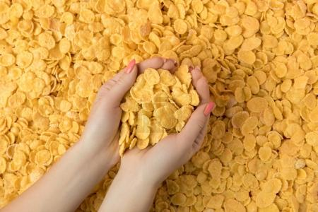 Photo for Top view of female hands holding crunchy tasty corn flakes - Royalty Free Image
