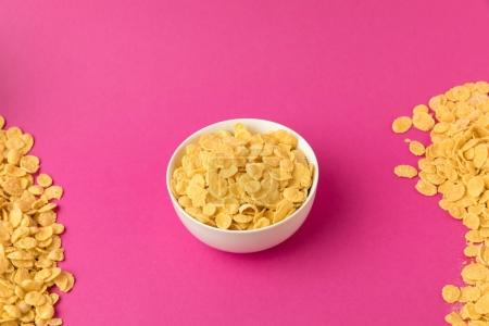 high angle view of white bowl with sweet healthy corn flakes isolated on pink