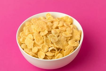 Photo for Close-up view of white bowl with sweet healthy corn flakes isolated on pink - Royalty Free Image