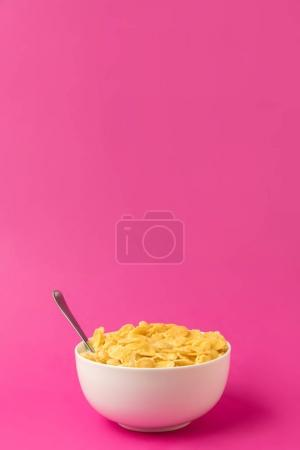 Photo for Healthy breakfast with tasty corn flakes and milk in bowl with spoon isolated on pink - Royalty Free Image
