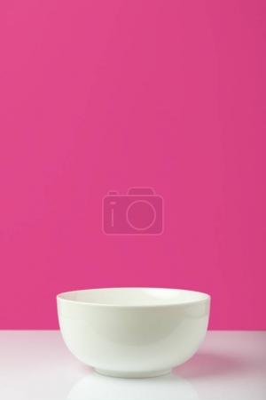 close-up view of empty white bowl with copy space on pink