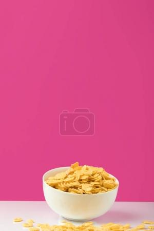 close-up view of white bowl full of sweet tasty corn flakes on pink