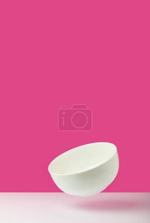 close-up view of empty white bowl on pink