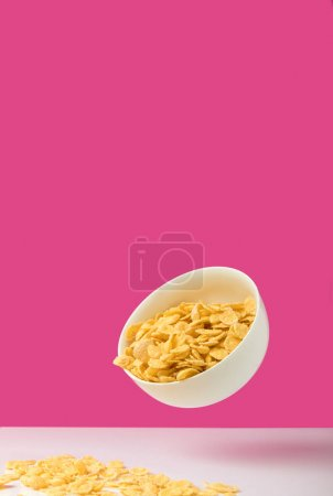 close-up view of white bowl full of tasty organic corn flakes on pink