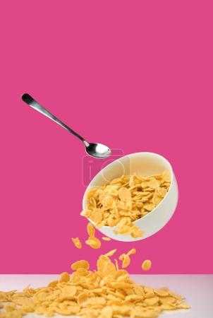white bowl with healthy tasty corn flakes and spoon on pink