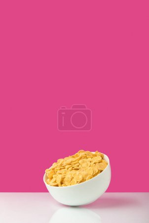 Photo for Close-up view of white bowl full of healthy tasty corn flakes on pink - Royalty Free Image