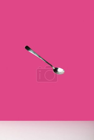 close-up view of single empty spoon isolated on pink