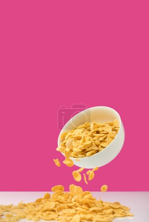 close-up view of white bowl with corn flakes pouring out on pink