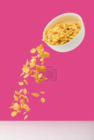 white bowl with corn flakes pouring out on pink