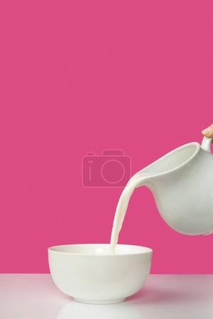 cropped shot of hand pouring fresh milk from jug to bowl on pink