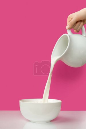 partial view of hand pouring fresh organic milk from jug to bowl on pink