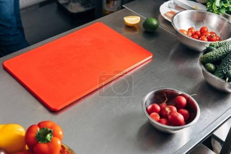 cutting board and fresh vegetables at restaurant kitchen